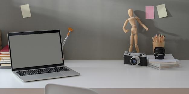 Comfortabele werkplek met opengeklapte laptop en vintage camera met kopie ruimte