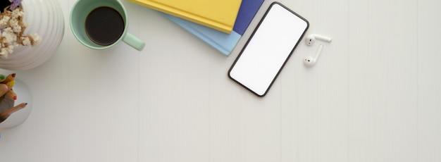 Comfortabele werkruimte met mock-up smartphone, boeken, draadloze hoofdtelefoon, koffiekopje en kopieerruimte