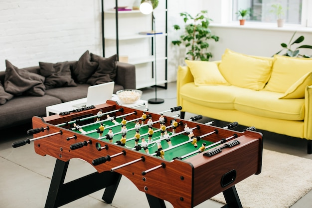 Comfortabele woonkamer met twee zachte banken en een handig tafelvoetbal in het midden
