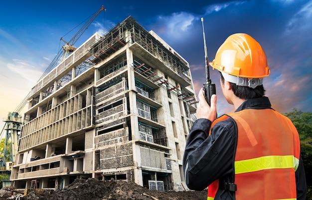 Commando bouwingenieur spreken vanaf draagbare radio op bouwplaats