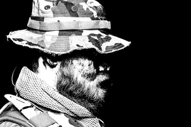 Commando soldaat, leger special forces veteraan, verkenning teamlid met gecamoufleerd door verf bebaarde gezicht, het dragen van boonie hoed, zijaanzicht, desaturated schouder portret op zwarte achtergrond