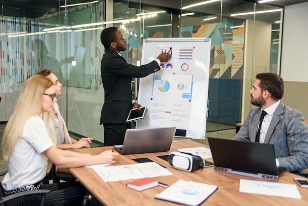 Commercieel professioneel team dat vergadering in bureau heeft. analyseren van statistieken van jonge bedrijven en hun startup projecten.