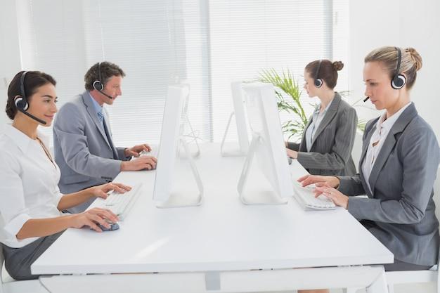 Commercieel team dat aan computers werkt en hoofdtelefoons draagt