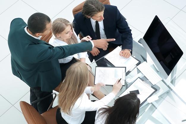 Commercieel team dat documenten in het bureau bekijkt