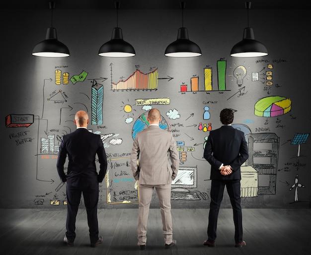 Commercieel team dat een nieuw complex project op muur bekijkt
