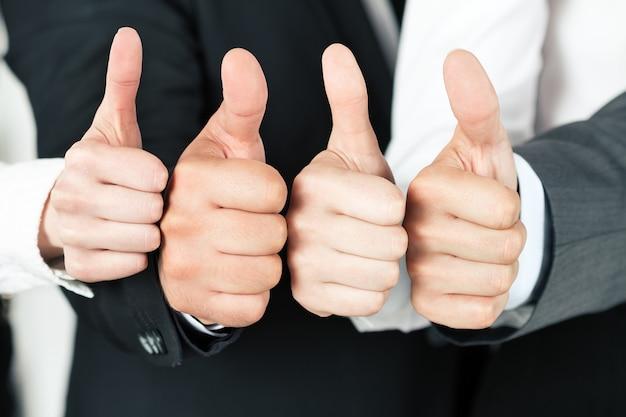 Commercieel team dat hun duimen benadrukt. van verschillende zakenmensen die omhoog wijst. concept van succes en groepswerk.