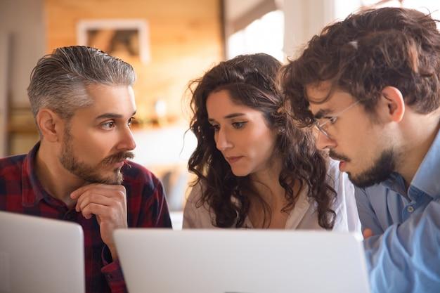 Commercieel team dat ideeën genereert voor projecten, met behulp van laptops