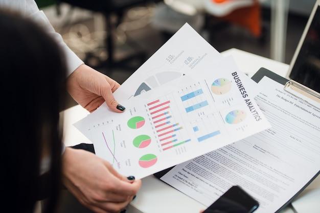 Commercieel team dat inkomensgrafieken met moderne laptop computers analyseert. sluit analyse en strategieconcept omhoog.