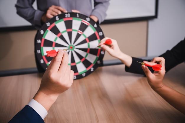 Commercieel team dat naar pijltjes richt die op de zaken van het doelcentrum richten, die het bedrijfsconcept richten