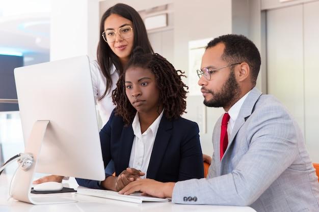 Commercieel team dat projectpresentatie op desktop samen bekijkt