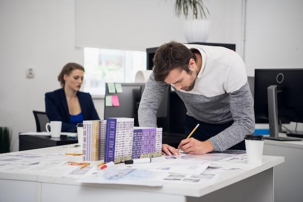 Commercieel team dat zich voorbereidt op de vergadering die de projecttekeningen controleert