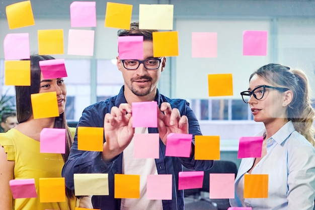 Commercieel team die ideeën op stickers in het bureau bespreken