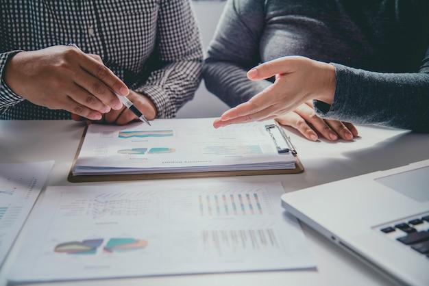 Commercieel team die met documentenfinanciën en grafiek werken in open plekbureau. verslag bezig.