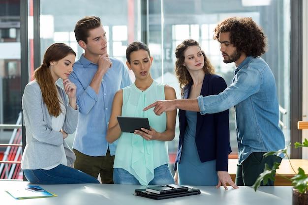 Commercieel team die over digitale tablet in vergadering bespreken