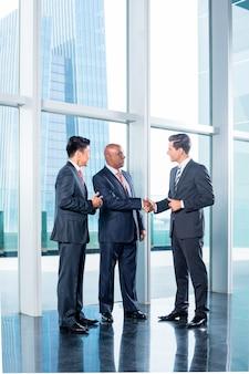 Commercieel team die overeenkomst en handdruk hebben