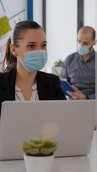 Commercieel team met medische gezichtsmaskers die samenwerken in het kantoor van een opstartend bedrijf