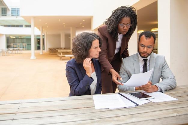 Commercieel team van drie documenten bestuderen