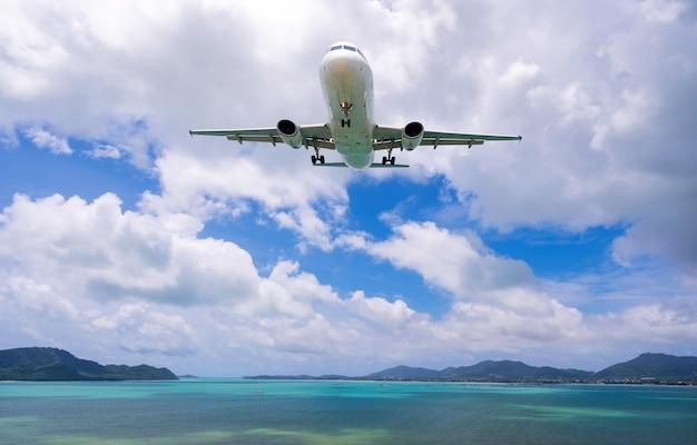 Commercieel vliegtuig dat boven zee en heldere blauwe hemel over mooie landschapsnatuur landt.