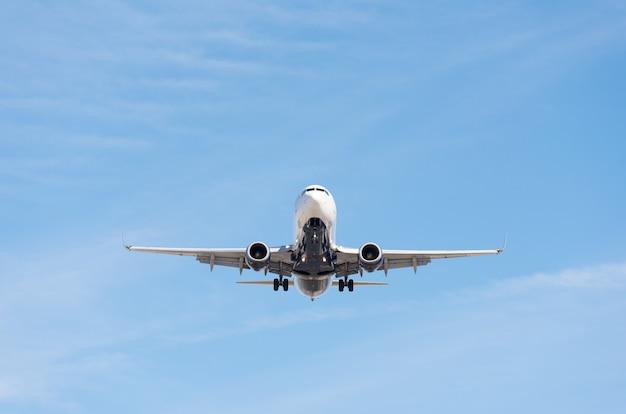Commercieel vliegtuig dat in blauwe uitgebreide hemel, volledige flap en landingsgestel vliegt