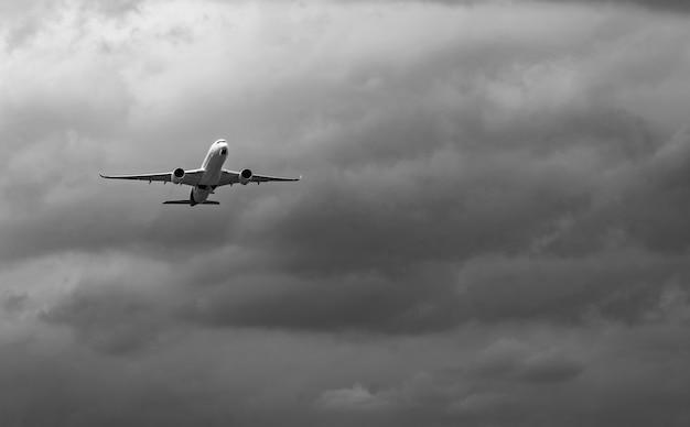 Commercieel vliegtuig op grijze hemel en wolken met exemplaarruimte. mislukte vakantie. hopeloos en wanhoop concept. humeurige lucht en transportvliegtuig. triest emotionele scène. achtergrond van vliegtuigvlucht.