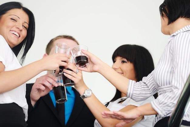 Commerciële groep die de glazen van een overwinningsholding met drank viert
