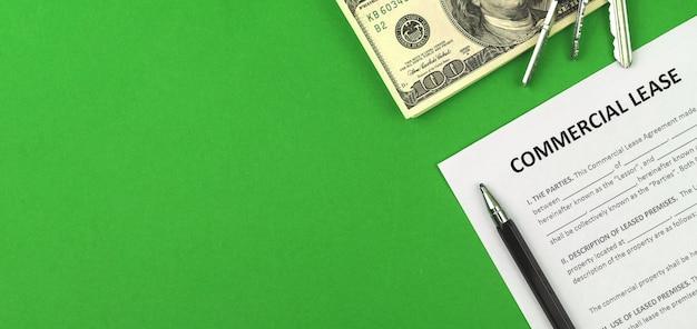 Commerciële huurovereenkomst. tabel met financiën en zakelijk document, huissleutels, pen en geld. groene achtergrond, banner en kopieer ruimtefoto