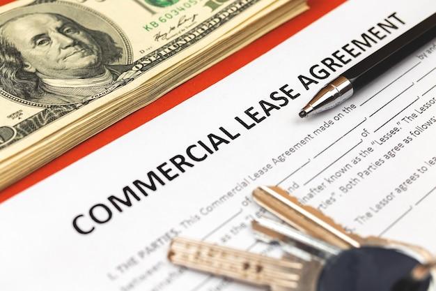 Commerciële lease-overeenkomst vorm close-up. huissleutels, pen en geld op bureau. close-up foto