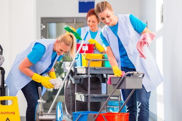 Commerciële schoonmakers doen het werk samen, drie vrouwen met een karretje aan het werk