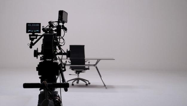Commerciële tv-opname en filmcamera set en cameraman in grote studio.