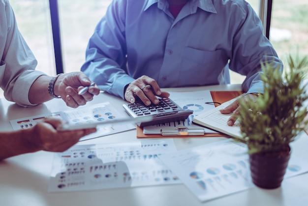 Commerciële vergaderings aziatische mensen twee mannelijke middelbare leeftijd die terwijl samen het zitten bespreken.