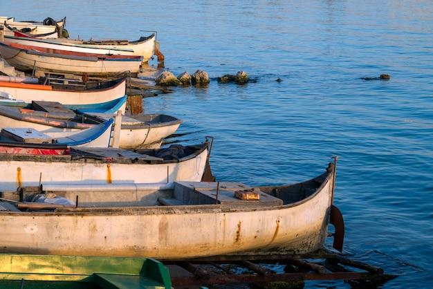 Commerciële vissersboten rusten op de kust door blauwe zee
