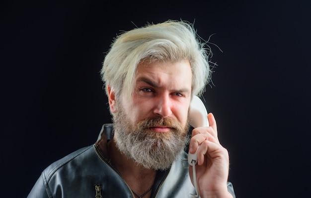 Communicatie bebaarde man met handset man praten op vaste telefoon serieuze man praten over retro