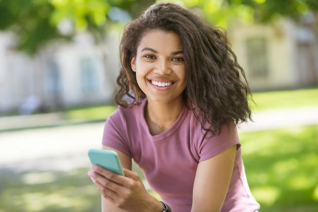 Communicatie. een schattig meisje in een roze t-shirt die tijd doorbrengt in het park en online kletst