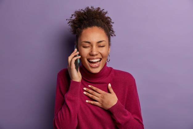 Communicatie, mensen en technologieconcept. afro-amerikaanse vrouw lacht zorgeloos terwijl ze op de mobiele telefoon praat, sluit de ogen en kan niet stoppen met lachen, hoort iets grappigs of heel positiefs van een vriend