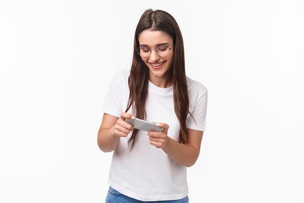 Communicatie-, technologie- en levensstijlconcept. portret van charismatisch grappig en gelukkig jong onbezorgd meisje in glazen