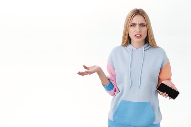 Communicatie, technologie en online concept. gefrustreerd blond meisje kan niet begrijpen wat er is gebeurd