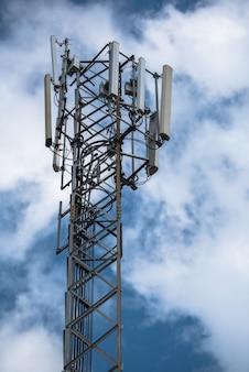 Communicatie toren met antennes zoals een mobiele telefoontoren, cellphonetoren, telefoonpool enz. op de hemel met wolkenachtergrond.
