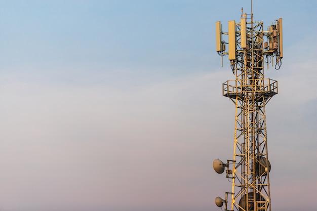 Communicatie toren met parabolische en gsm-antennes op blauwe hemel met kopie ruimte.