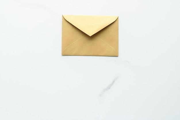Communicatienieuwsbrief en bedrijfsconceptenveloppen op marmeren achtergrondbericht