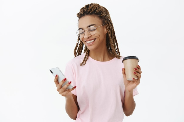 Communicatieve sociale knappe moderne donkere vrouwelijke student met dreadlocks in roze t-shirt