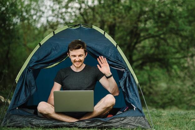 Communiceer met familie, familie online op laptop in tent in de natuur. man briefing het team op de conferentie of overleg op afstand, man werknemer spreekt praten over videogesprek met collega's.