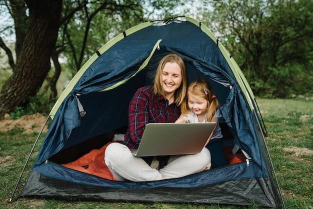 Communiceer met familie, familie online op laptop in tent in de natuur. vrouw werknemer spreken praten over videogesprek met collega's. moeder die met kind werkt. kind maakt lawaai en stoort moeder.