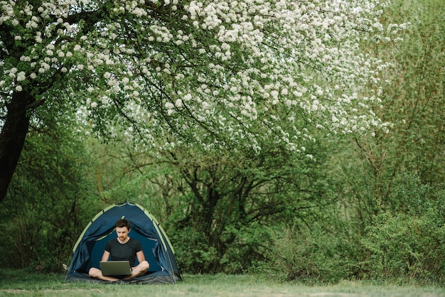 Communiceer met familie, familie online op laptop in tent in de natuur