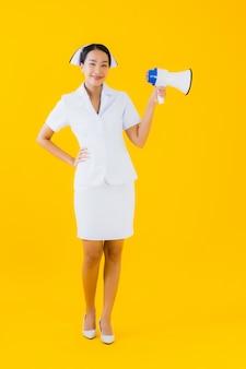 Communiceert de mooie jonge aziatische de vrouwen thaise verpleegster van het portret met megafoon voor