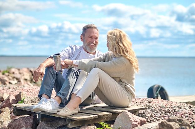 Communiceren man en vrouw zittend op de grond in de buurt van zee