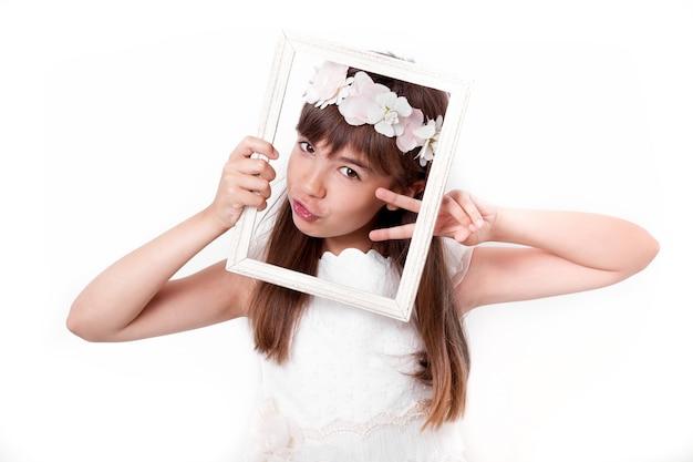 Communie meisje grimassen met een frame op haar gezicht