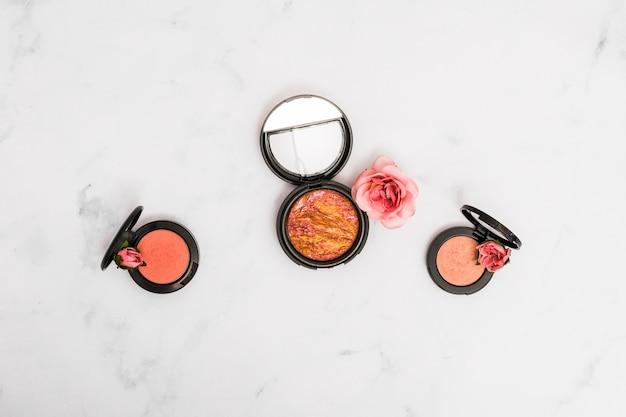 Compact gezichtspoeder met roos en knoppen op marmeren gestructureerde achtergrond