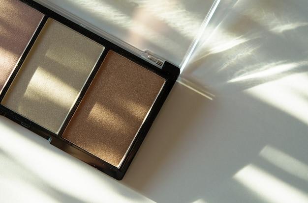 Compact oogschaduwpalet of illuminator. het concept van mode- en schoonheidsindustrie. natuurlijk hard licht, diepe schaduwen.