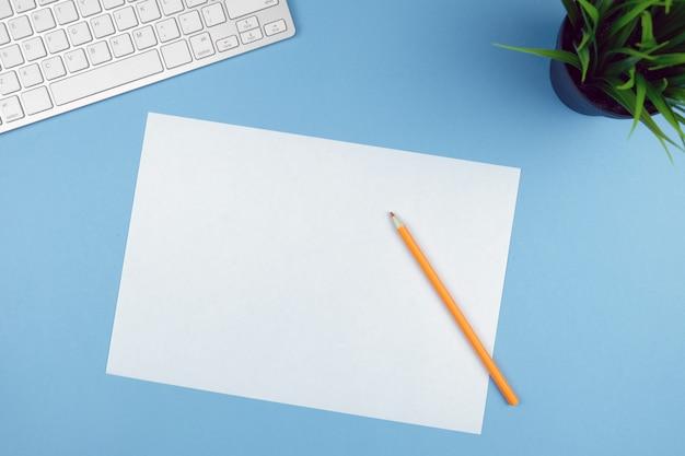 Compact wit toetsenbord op een blauwe achtergrond met een plant, wit papier en potlood.