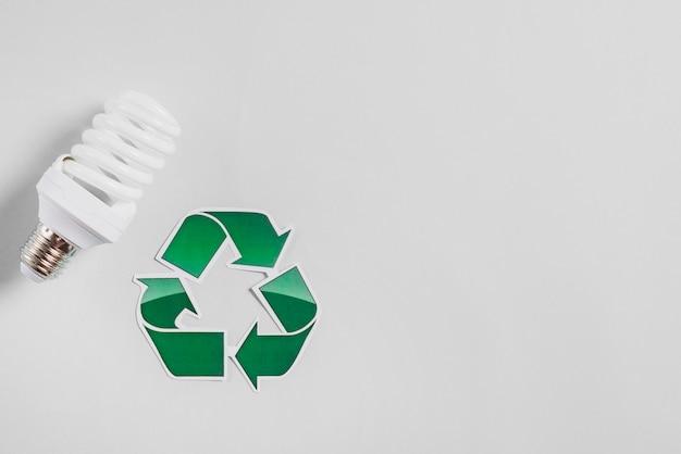 Compacte fluorescerende gloeilamp en recycle pictogram op witte achtergrond